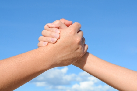 Partner hand between a man and a woman on blue sky background, Teamwork Stock Photo - 14970789