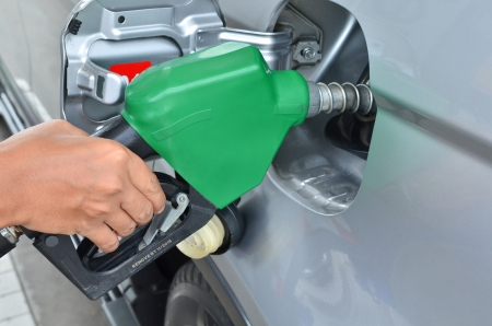 benzine: A man pumping gas in to the tank