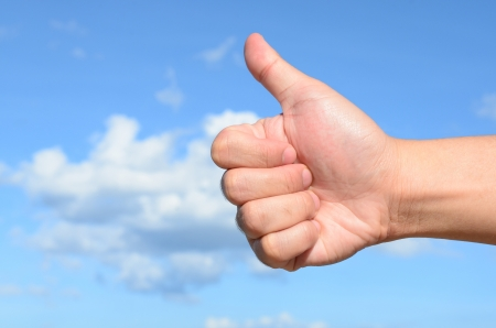 Male hand showing thumb up sign on blue sky background Standard-Bild