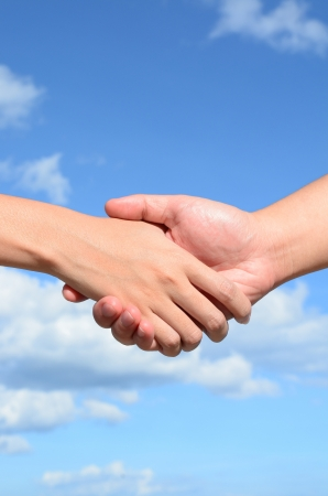 Partner hand between a man and a woman on blue sky background, Teamwork Stock Photo