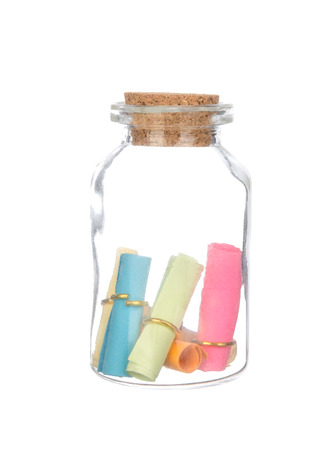 castaway: colorful paper in the bottle with cork isolated on white background Stock Photo