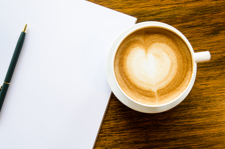 A cup of coffee with heart shape, pen and open blank book on wood background