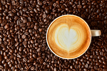 heart symbol: A cup of coffee with heart shape on coffee bean background