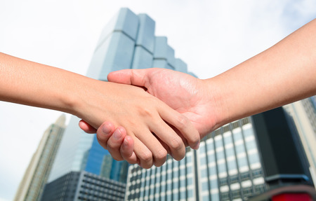 achievement concept: Partner hand between a man and a woman on building background, Teamwork Stock Photo