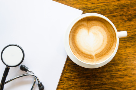 A cup of coffee with heart shape, Stethoscope and open blank book on grungy wood background Stock Photo