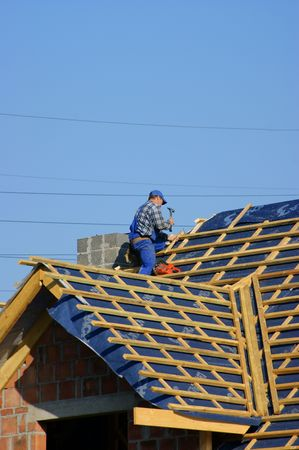 an erection: Man building construction roof Stock Photo