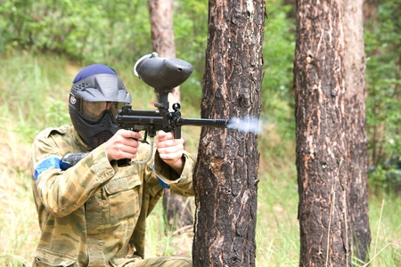 Paintball player shooting in the forest