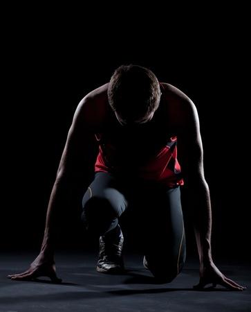 Athlete ready to start on black background