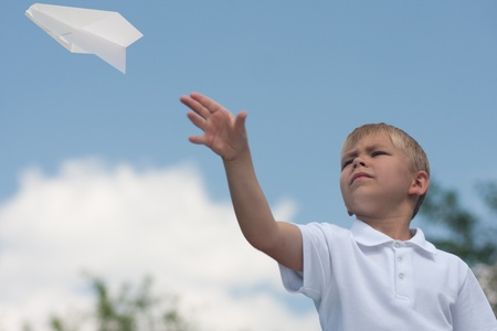 Boy with paper plane outdoor photo
