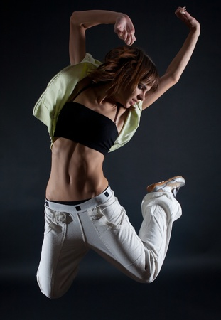Young attractive woman jumping on black background