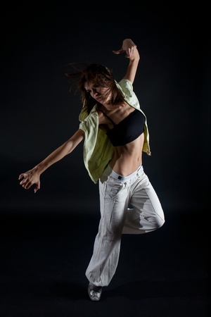 Young attractive woman dancing on black background