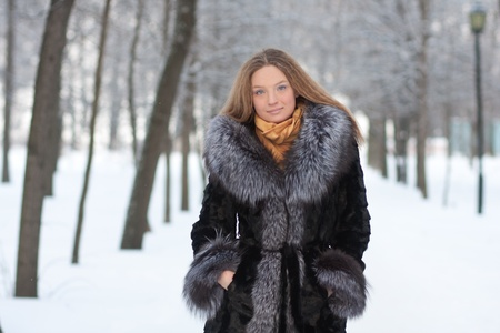 fur hood: portrait of young woman in winter park with long hair
