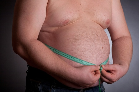 big belly: Fat man holding a measurement tape on dark background