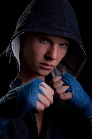 Young man in a hood on black background photo
