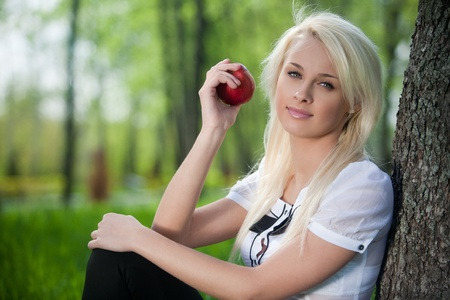 Young blond woman sits near tree in park with the apple in her hand