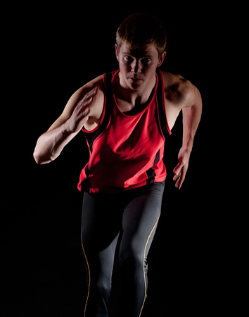 Young male runner on dark background photo