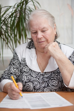 Senior woman writing something with a pen photo