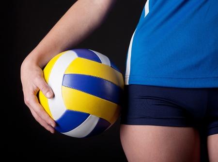 voleibol: Parte del cuerpo de la mujer con la pelota en el fondo oscuro Foto de archivo