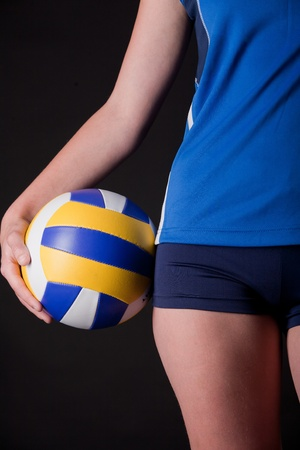 female volleyball: Part of womans body with ball on dark background