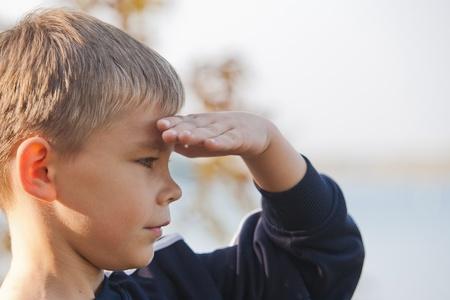 loin: Boy regardant � une distance avec les yeux ombrag�s