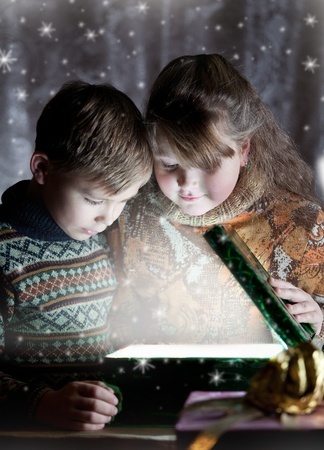 Children opening christmas magic present Stock Photo