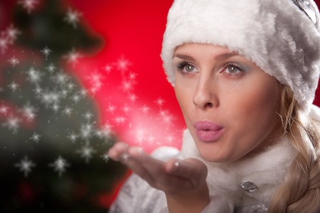 Beautiful woman in Christmas costume blowing snow form hand photo