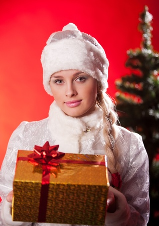 plait: Portrait of beautiful girl wearing santa claus clothes with christmas present