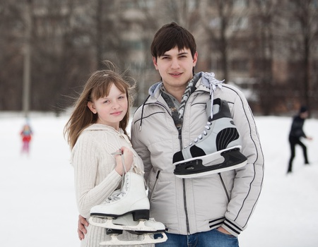 Portrait of young couple on ice skate rink outdoors  photo