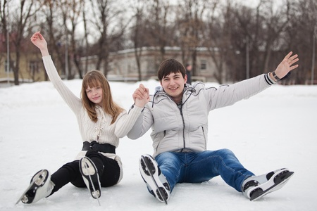 Young couple having fun on ice skate rink outdoors  photo