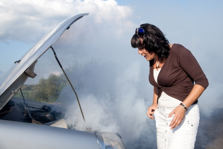 Scared woman nearby the smoking car