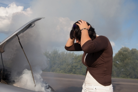 Frustrated woman looking at smoking car engine photo