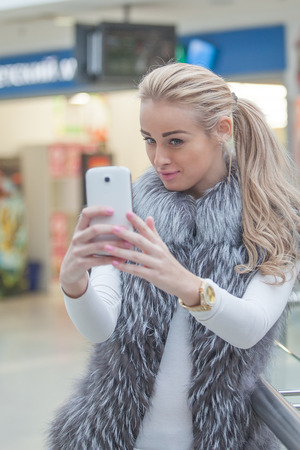 Beautiful woman posing for a selfie with a smart phone,