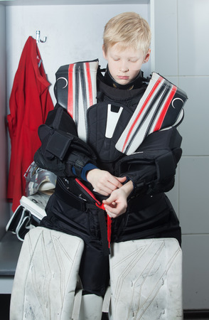 protector: Young boy in goalie uniform fasten chest & arm protector Stock Photo