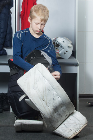 goalie: Young boy in goalie uniform fasten leg pads