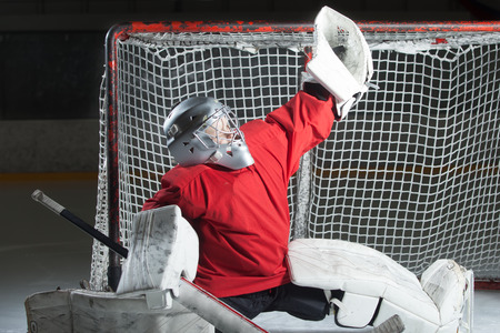 nets: Young goalkeeper catching a puck in split position. Focus on puck. Stock Photo