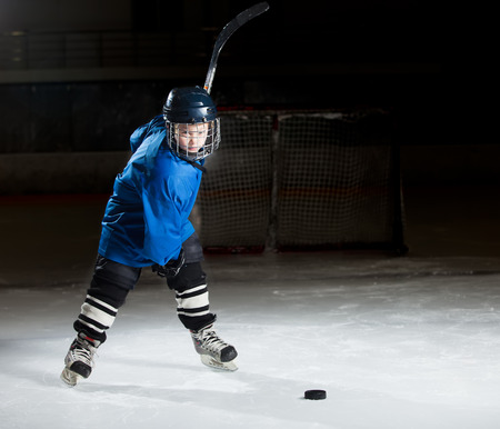 hockey skates: Young hockey player ready to make a strong shot against dark background Stock Photo