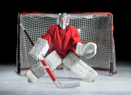 A young ice-hockey goaltender in a ready position