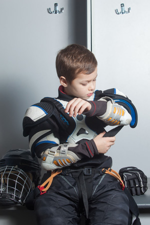protector: Young boy in hockey uniform fasten chest & arm protector