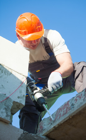 Builder worker with hammer drill