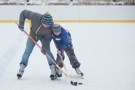 Father with his little son playing ice hockey