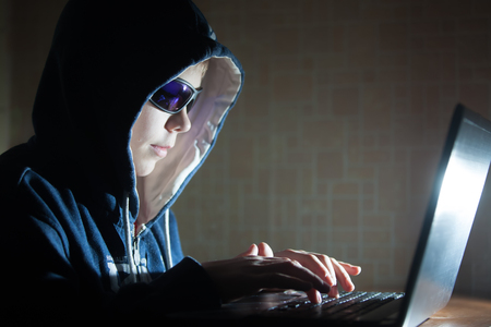 Youmg Hacker Typng on a Laptop