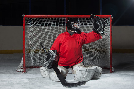 Young goalkeeper catching a flying puck