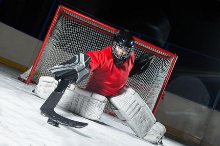 Hockey goalie blocking a puck with stick