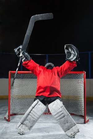 elated: Hockey goalkeeper standing elated with arms raised up above her head