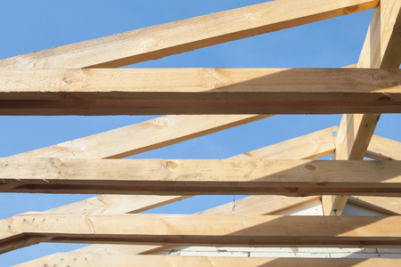 roof framing: Wooden roof with rafter style framing against a blue sky Stock Photo