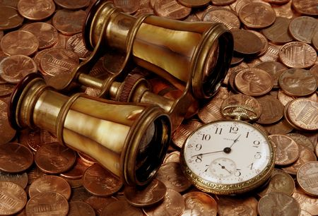 An old brass set of opera glasses and an antique pocketwatch atop US coins portrays the search for financial clarity Фото со стока