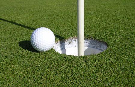 -ゴルフ ・ ボールがパッティング グリーンでカップの非常に端に近い