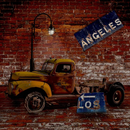 Los Angeles - an old broken down truck under a light with a L.A. freeway sign that has rusted and fallen apart. Surreal with brick background.