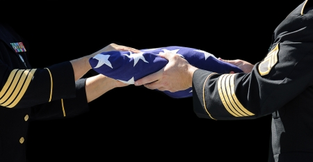 Two Army Officers handle the flag with reverence during a funeral ceremony where respects are paid to a fallen military member