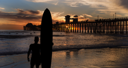 Long board surfer silhouette. A male surfer watches other surfers near the Oceanside Pier in San Diego, California. Stock Photo